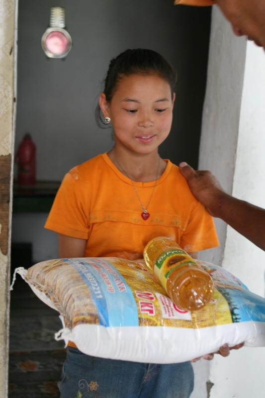 몽골에서 아이에게 쌀을 나누어 쌀을 받고 좋아하는 모습